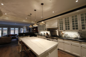 Modern white kitchen with white marble counter top and pendant lighting.