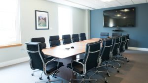 Modern meeting roof with large television, webcam and meeting table and chairs.