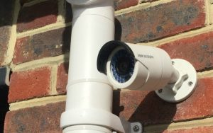 Hikvision security camera mounted on a brick wall next to a drainage pipe.