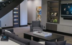 Modern angular lounge in earthy neutral colours. The room is filled with modern technology.