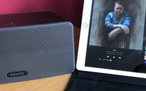 Sonos music speaker and a tablet showing the artwork for an album.